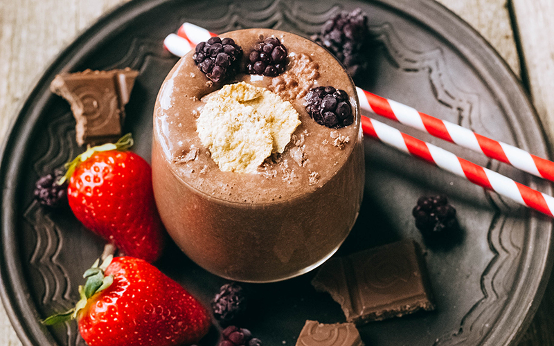 protein shakes made of chocolate with a strawberry on the side
