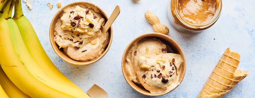 a photo of bananas next to two containers of banana-peanut butter nice cream