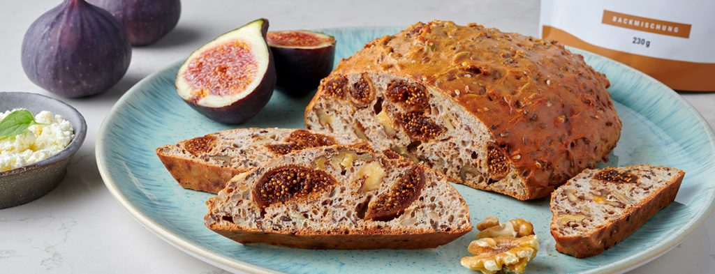 a loaf of fig and walnut bread next to a halved fig on a light-blue plate