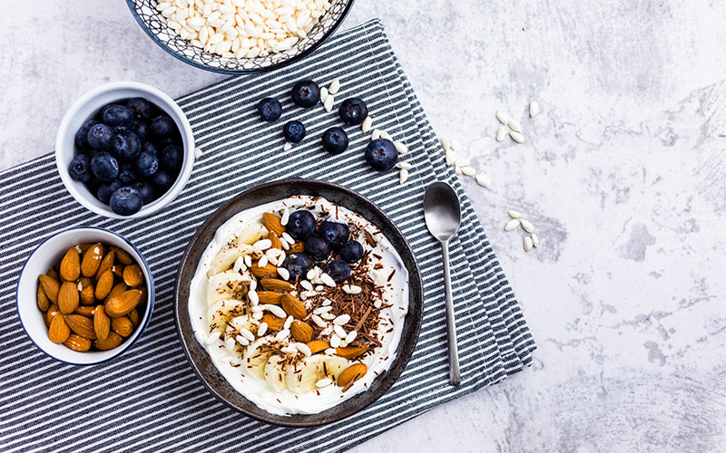 Photo from above of a bowl of overnight oats with nuts and berries, a delicious way to start changing to healthy habits.