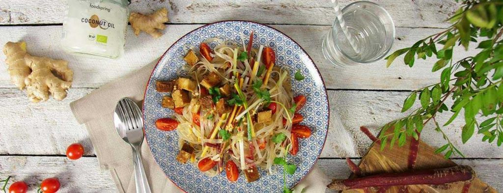 A photo from above of glass noodle salad with tofu, garnished with bright red accents, and with a spoon next to the plate