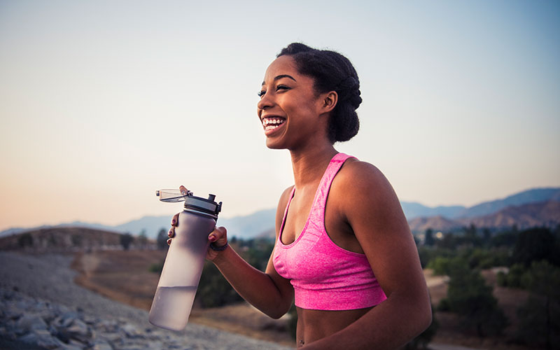 A woman of color holds a water bottle and smiles outdoors, experiencing the high of endorphins