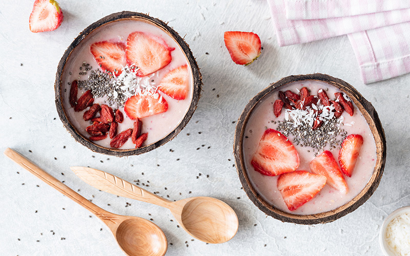 A photo of two bowls seen from above, topped with aphrodisiac foods including strawberry slices and goji berries