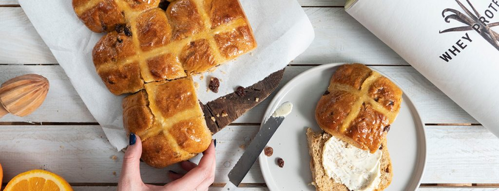 A light-skinned hand reaches for hot cross buns on a plate