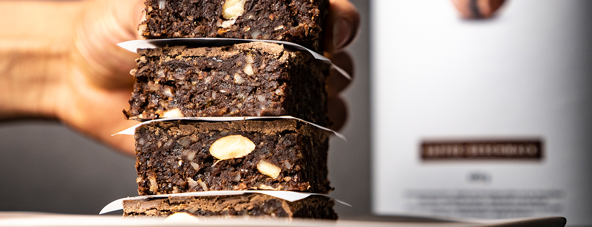 A medium-skinned hand in the background reaches for the top brownie on a stack of raw vegan coffee brownies, packed with chunks of nuts and deliciousness
