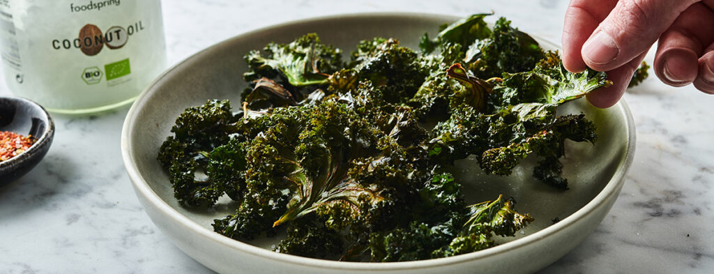 A light-skinned hand reaches for a vibrant green crisp from a bowl of kale chips