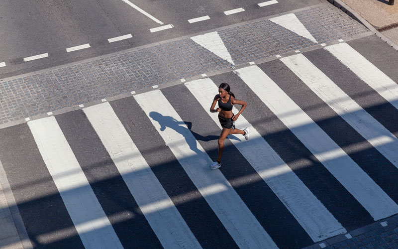 a woman of color runs for endurance training as she crosses a road on a large zebra-striped crosswalk. She is seen from a distance, from above.
