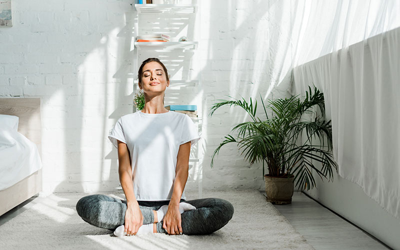 how to reduce stress - meditation like this photo of a woman in her living room sitting and closing her eyes