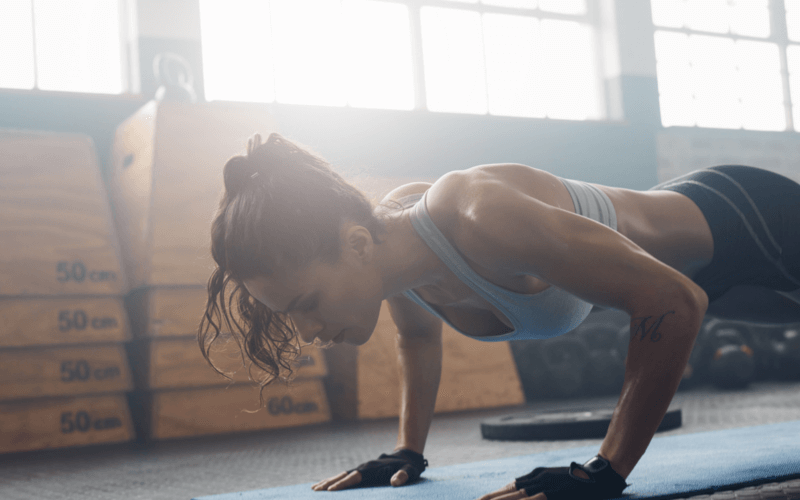 A woman does pushups as part of her extreme HIIT workout indoors