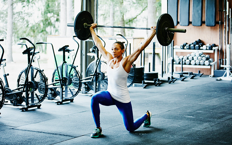 A woman of medium skin tone does barbell lunges using motivation to help her keep going.
