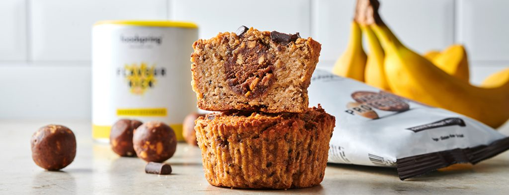 a stack of two paleo muffins with foodspring's Protein Balls in the background as well as two bananas