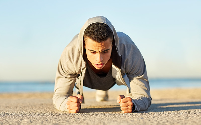 A man of color wearing a gray hoodie does a plank outdoors