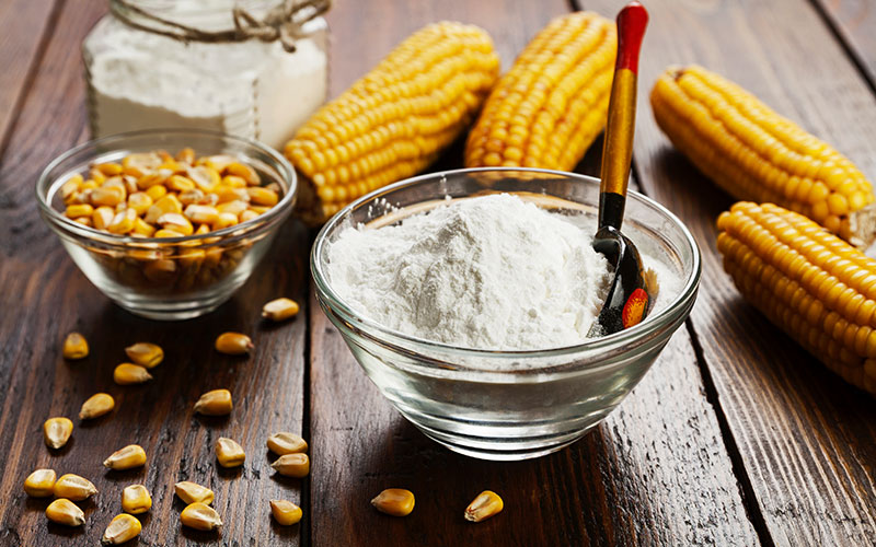 Four ears of corn sit next to a bowl of corn starch and a smaller bowl of corn kernels