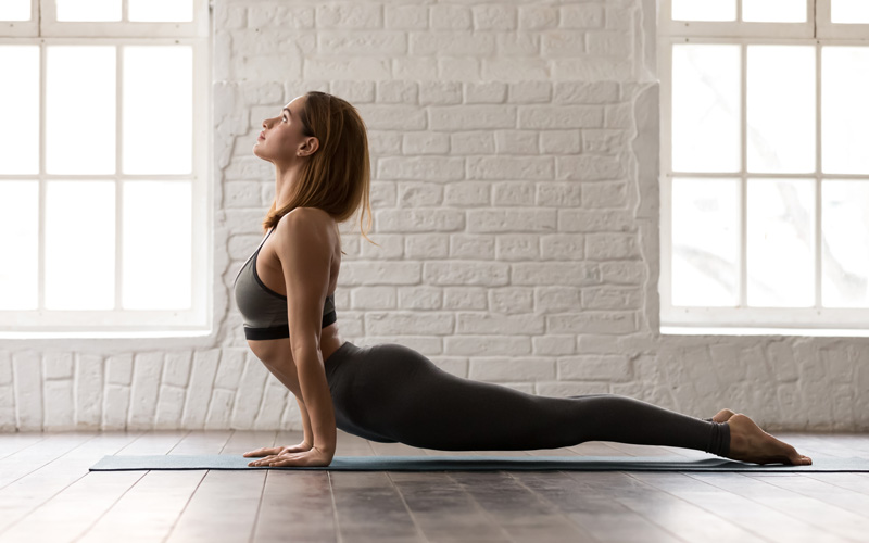 A white woman does yoga on an active recovery day