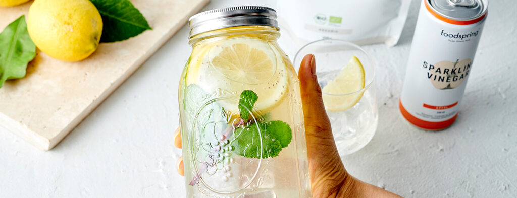 a hand with medium skin tone holds a sealed Mason jar of infused water. Inside the jar are a few lemon slices and mint leaves. Behind the jar, a can of foodspring's Sparkling Vinegar Water can be seen.