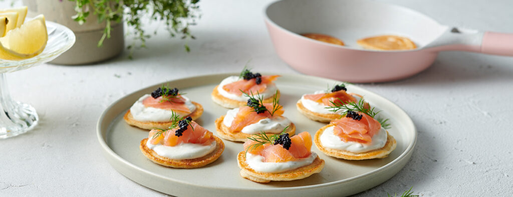 A plate of smoked salmon blinis garnished with dill and caviar