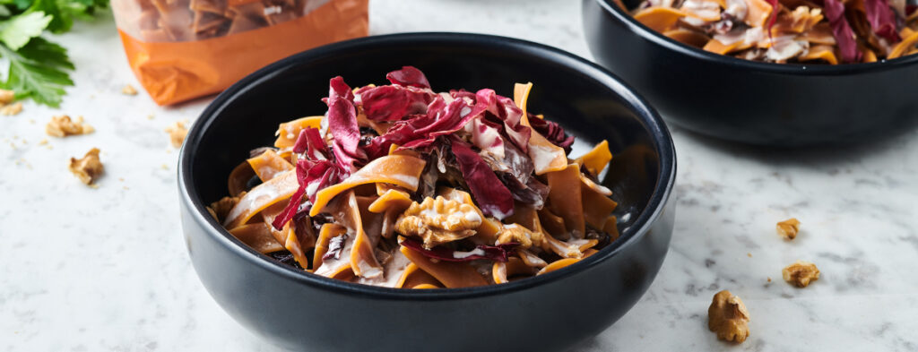 a photo of a black bowl holding protein pasta with radicchio