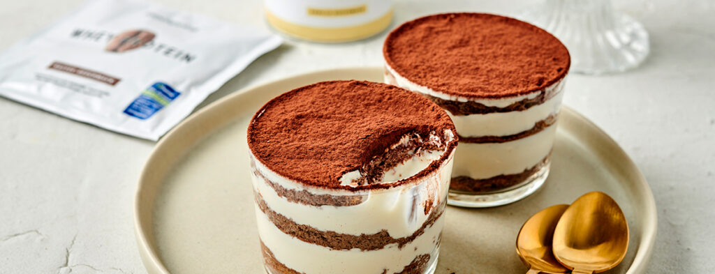Two glasses filled with layers of tiramisu. One has a crescent-shaped scoop taken out of it.