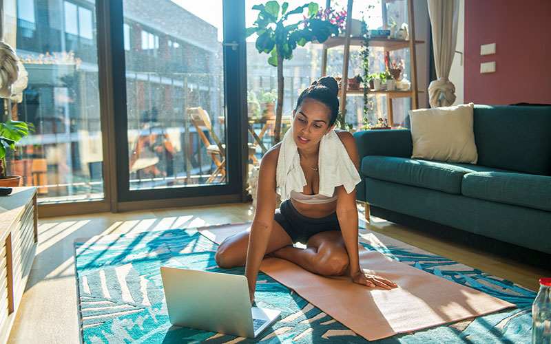 A woman of color sits on a yoga mat in a sunlit living room with a towel wrapped around her neck, with her laptop open to do a home workout