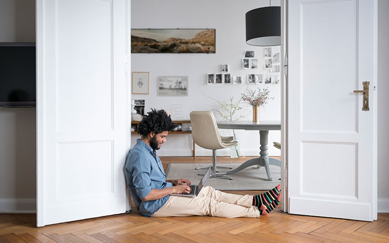 how to set up a home office so it doesn't look like the white man in this picture, sitting with his back against a doorframe and hunching over a laptop in his lap