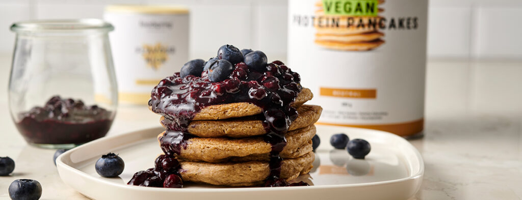 a stack of Vegan Blueberry Pancakes drizzled with a blueberry sauce