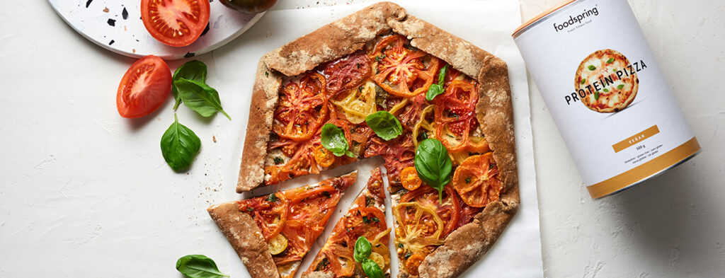 A vegan tomato galette topped with bright red and yellow tomato slices and garnished with fresh basil leaves sits on a white background. In one corner of the image is a canister of foodspring's Protein Pizza mix