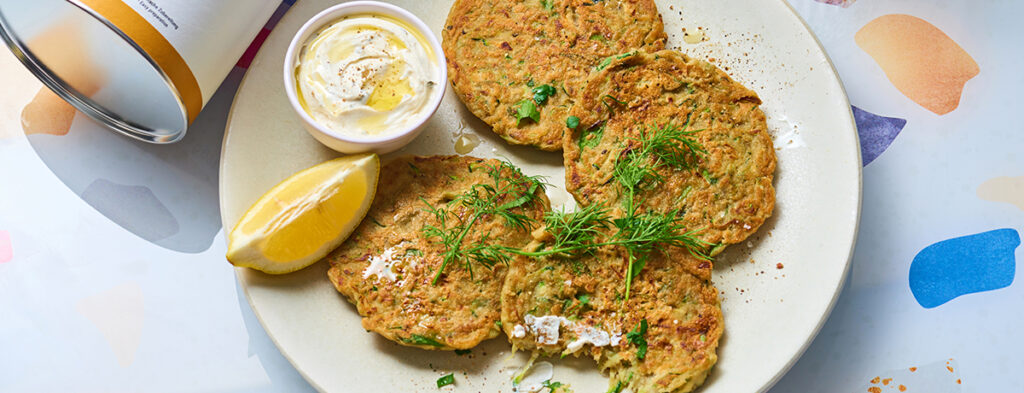 A plate of vegan zucchini pancakes topped with fresh green herbs. A quarter lemon and a bowl of cream-colored dip sit on the side.