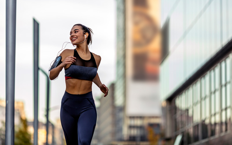 A woman of color smiles to her side as she does an outdoor workout, running in a city