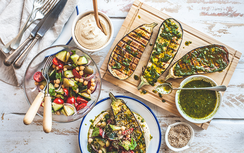 Vegan grilling spread with aubergines sliced lengthwise and topped with a medley of fresh vegetables and herbs