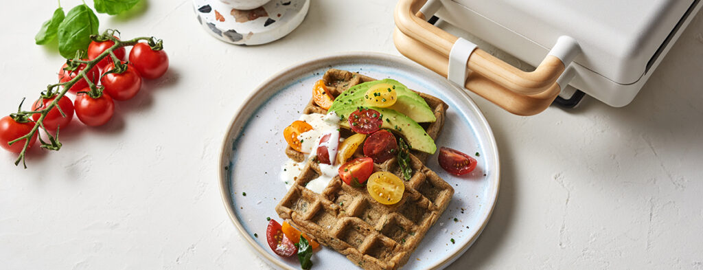 A plate of vegan, savory waffles studded with green herbs, topped with a colorful red-and-green mix of mini tomatoes and avocado slices