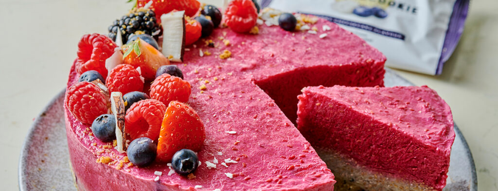 a fruity-red chia pudding cake topped with fresh berries, with one slice missing and another pulled partially out to show off the layer of chia pudding and the protein cookie crust