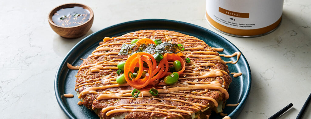 A Vegan Protein Okonomiyaki sits on a dark blue plate, drizzled with orangey-red sauce and topped with sliced vegetables