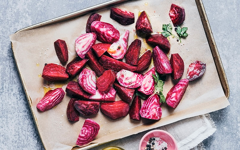 a baking tray with beet quarters of a candy cane beet
