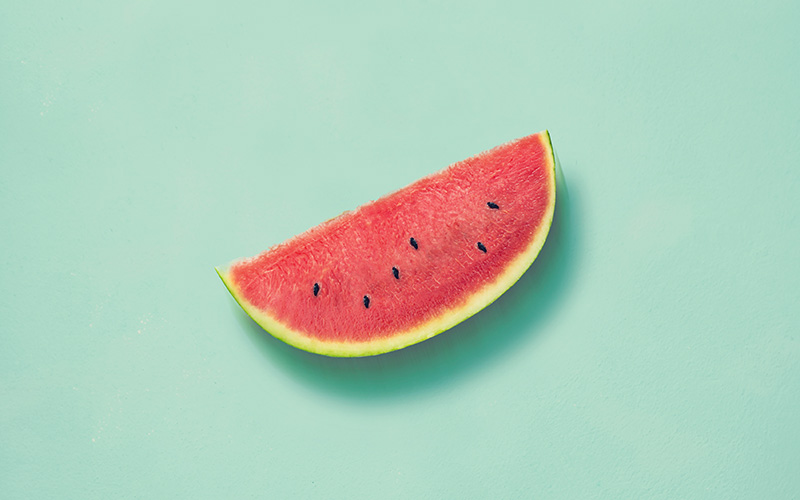 A slice of watermelon on a turquoise background as a great example of cooling foods for summer