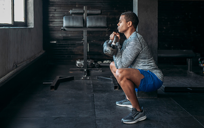 A man of color in sports gear does a goblet squat indoors, holding a kettlebell.