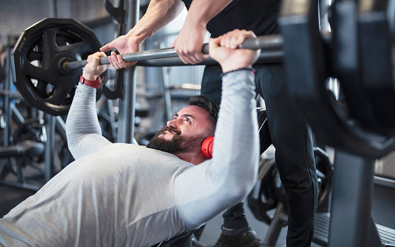 A white bearded man performs an upper body workout for men, doing a bench press while being spotted by another pair of white hands.