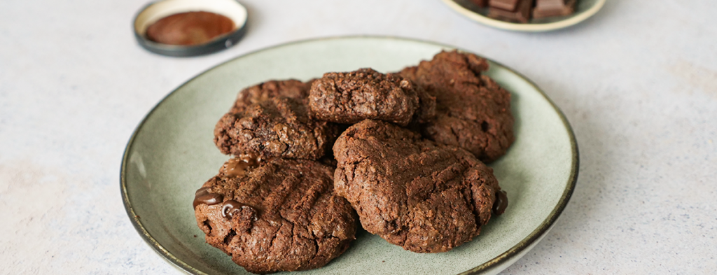 A light-green plate of filled vegan chocolate cookies