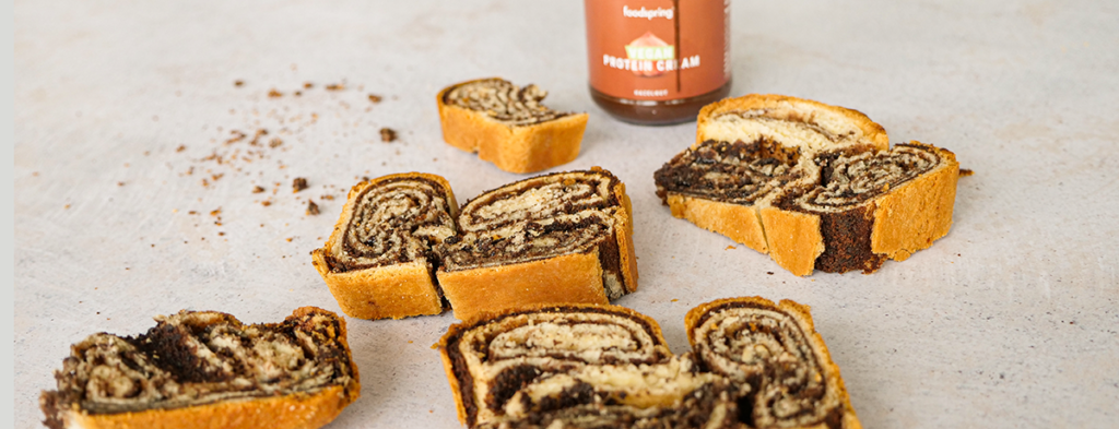 Several slices of golden-brown and chocolate-brown rolled vegan chocolate babka sit on a neutral white surface with a jar of Vegan Protein Cream behind them.