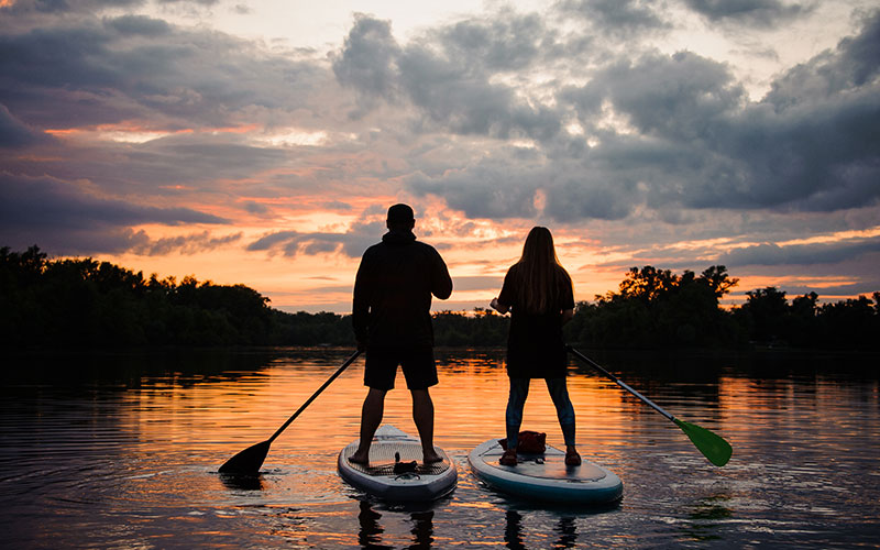 Two people seen in silhouette from behind doing outdoor sports. They are stand-up paddling.
