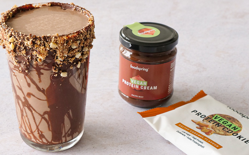 A glass of vegan protein cream and a package of vegan protein cookies sit next to a fudgy protein shake drizzled with the protein cream on the outside.