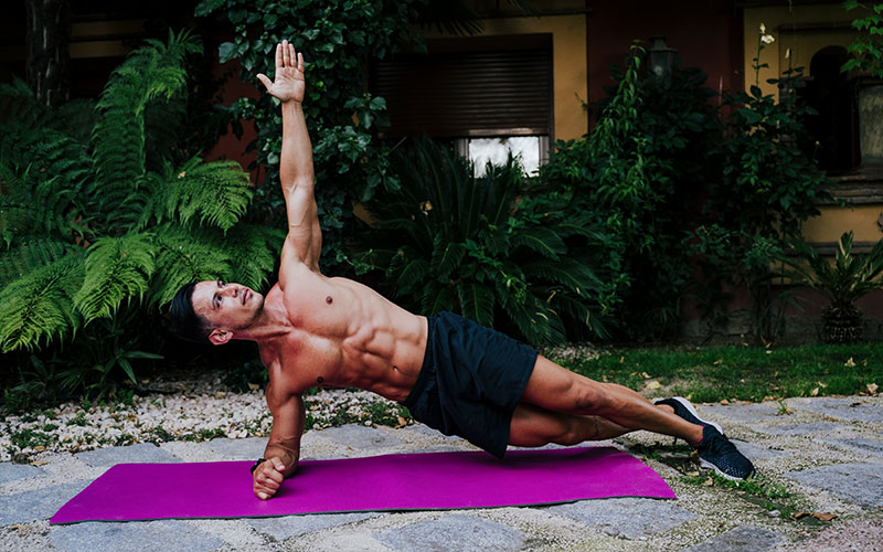 A white man does a side plank to work on his side abs