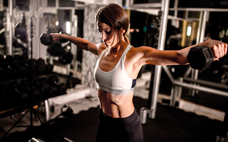 A white woman does an upper body workout for women in the gym.