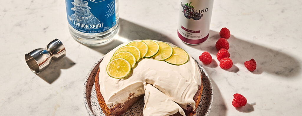 A raspberry gin and tonic cake seen from above. The creamy frosting forms a decadent layer on top, while a garnish of thin lemon slices fans out on top of it.