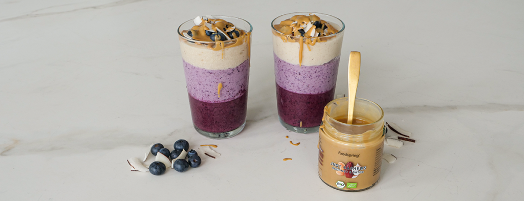a fruity blueberry coconut protein shake with cashews