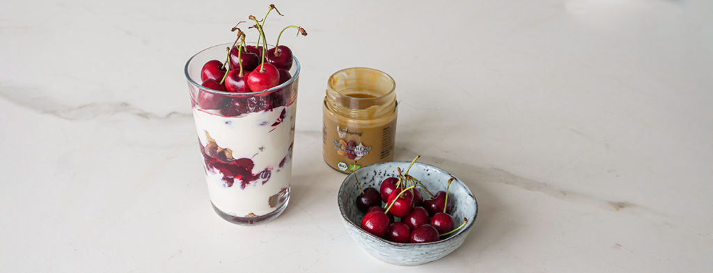 Cherry Protein Parfait with waffles, sitting next to a bowl of cherries and a jar of Just Nuts