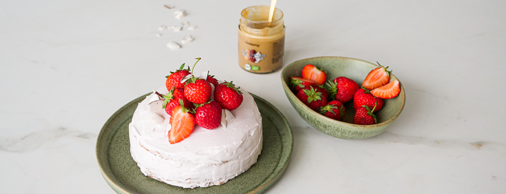 A pink-tinted crepe cake covered with fresh strawberries sits on a green-gray plate