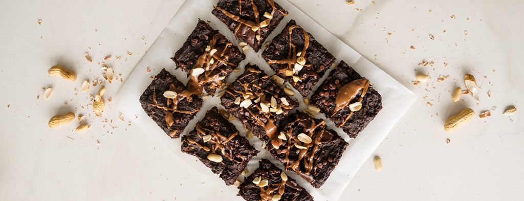 A photo of zucchini chocolate brownies topped with nuts and a drizzle of nut spread