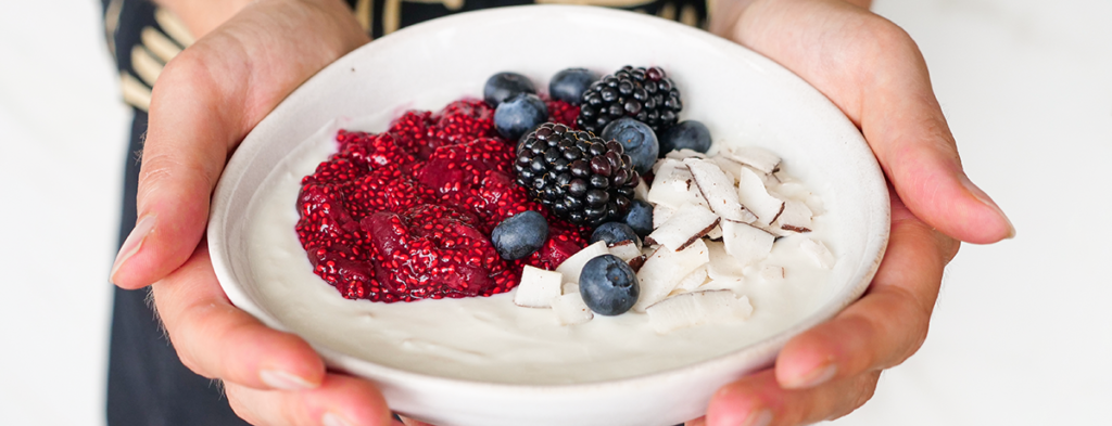 two white hands hold a bowl of yogurt topped with fresh berries, coconut chips, and chia cherry jam