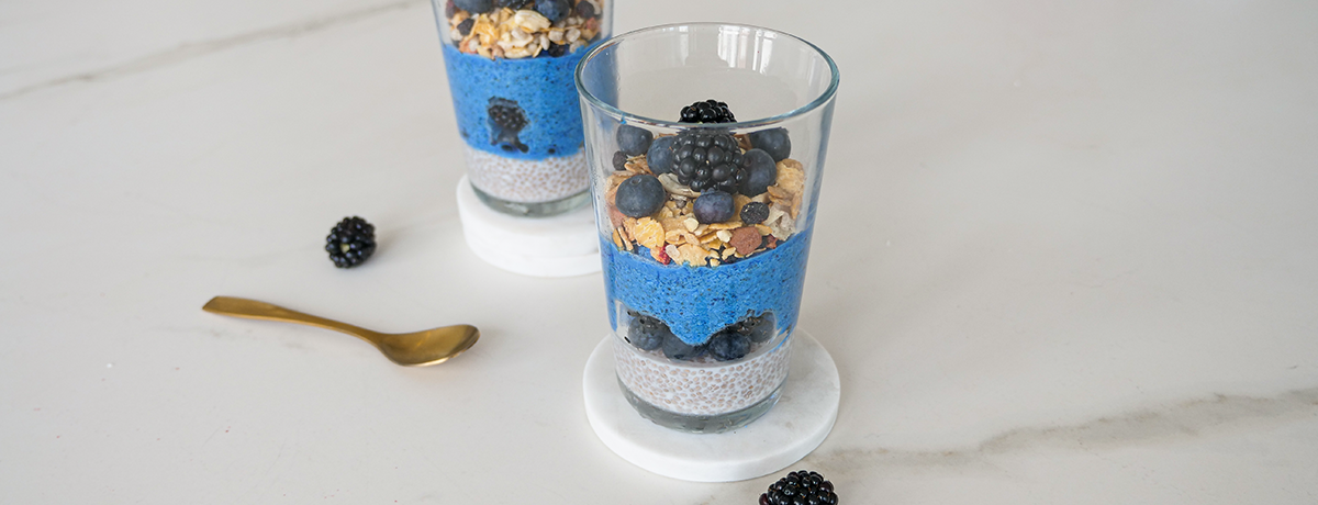 Spirulina breakfast bowl mix layered in a glass with yogurt, granola, and berries