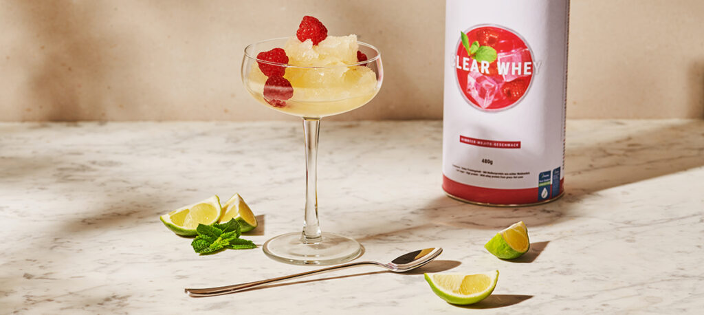 A bowl-shaped stemmed glass of raspberry mojito ice cream, garnished with fresh raspberries, stands next to two lime slices and a container of Raspberry Mojito Clear Whey